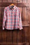 La camisa está colgando en una cerca de madera Imagenes de archivo