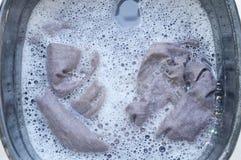 La camisa gris empapa en la disolución detergente del agua del polvo en el lavabo plástico negro Fotografía de archivo libre de regalías