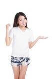 La camiseta blanca de la demostración de la sonrisa de la muchacha con la mano introduce Foto de archivo libre de regalías