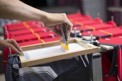La camiseta hecha a mano de la impresión de la pantalla, trabajadores está funcionando foto de archivo libre de regalías