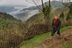 La campagna Cina montagnosa, agricoltore, cammina lungo un recinto di vimini. Immagini Stock