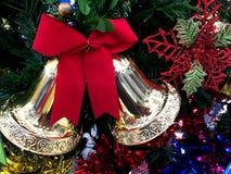 La campana de oro con la cinta roja adorna en el árbol de navidad fotografía de archivo