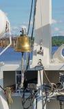 La campana del ` s de la nave en el arco con los elementos del aparejo de la nave en un día soleado verticalmente Imagen de archivo