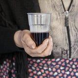 La campesina ofrece un vidrio de vino rojo Foto de archivo