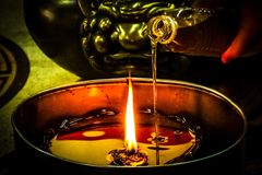 la candela di illuminazione vicino versa l'olio al santuario Immagini Stock