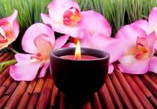 La candela e l'orchidea della stazione termale fioriscono per aromatherapy immagine stock libera da diritti