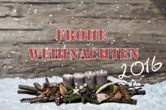 La candela grigia bruciante della decorazione 2016 di Buon Natale ha offuscato il tedesco del messaggio di testo della neve del f Fotografie Stock