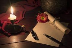 La candela illumina lo scrittorio in cui la lettera Immagini Stock Libere da Diritti