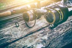 La canne à pêche embrayent l'amorce de pêcheur à la ligne de bobine de roue de rotation de fond concentrée Image stock