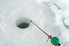 La canne à pêche pour la pêche d'hiver est sur la glace Attente des poissons mordant sur la pêche d'hiver Photographie stock libre de droits