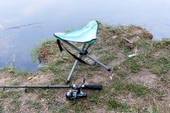 La canne à pêche, tabouret se pliant, flottent et l'autre vitesse sur la berge Image libre de droits