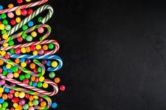 La canne de sucrerie de Noël avec la sucrerie se laisse tomber au-dessus du fond noir avec photographie stock