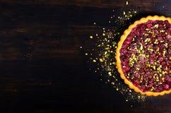 La canneberge délicieuse de homamade, tarte de cerise avec des pistaches, a saupoudré le sucre sur le fond en bois foncé pour Noë Image stock