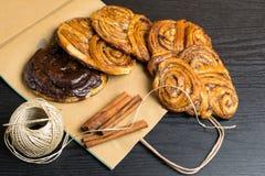la cannelle douce faite maison, chocolat, pavot roule sur le sac de papier avec des bâtons des cinnamons déserts photos stock