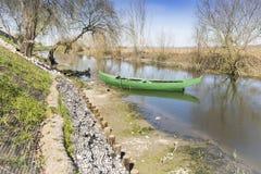 La canoa verde parqueó en la orilla de un río imagen de archivo libre de regalías