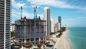 La cantidad aérea de la construcción inacabada del hotel entre hoteles lujosos hermosos en las islas soleadas vara, Miami almacen de video