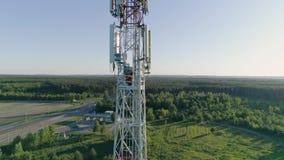 La cantidad aérea que mantenía la antena celular, trabajador se vistió en uniforme y el casco sube la escalera almacen de metraje de vídeo