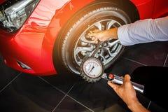 La cantidad asiática de la medida de la inspección del coche del hombre infló los neumáticos de goma fotografía de archivo