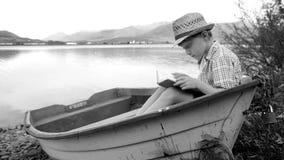 La cantidad blanco y negro de un muchacho que se sienta en un barco en el lago y lee almacen de metraje de vídeo