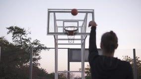 La cantidad de Stedicam de la chica joven de la parte trasera hace un tiro a la red del baloncesto Al aire libre, árboles en el f almacen de metraje de vídeo