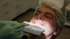 La cantidad de un dentista que comprueba un joven sirve la sombra del color del diente almacen de video