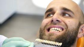 La cantidad de un dentista que comprueba un joven sirve la sombra del color del diente almacen de metraje de vídeo