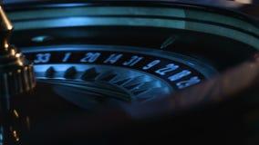 La cantidad del primer de la bola blanca está haciendo girar en una rueda de ruleta rusa y después entra en una ranura en una mes metrajes