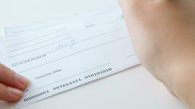La cantidad del primer 4k de la mujer joven que llena el cheque del banco de 100 dólares para la caridad purposes almacen de video