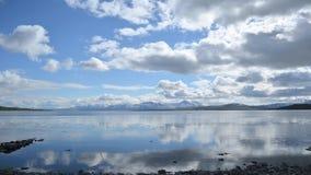 La capa rápida de la nube sobre las montañas majestuosas y el fiordo azul reflexivo riegan el timelapse metrajes