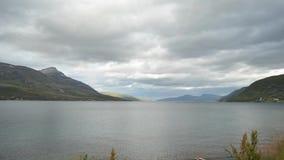 La capa rápida de la nube sobre las montañas majestuosas y el fiordo azul riegan el timelapse almacen de video
