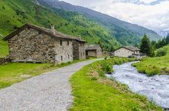 La capanna del pastore di pietra alpino in un villaggio agricolo nei precedenti delle alpi Immagine Stock Libera da Diritti