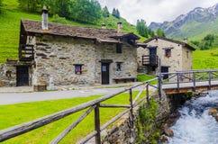 La capanna del pastore di pietra alpino in un villaggio agricolo nei precedenti delle alpi Fotografia Stock Libera da Diritti