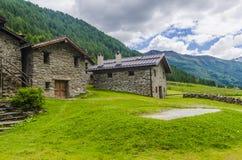 La capanna del pastore di pietra alpino in un villaggio agricolo nei precedenti delle alpi Fotografia Stock