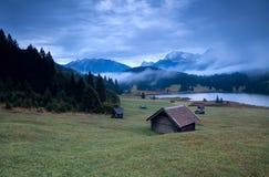 La capanna di legno e la mattina annebbiano sopra il lago Geroldsee Fotografia Stock Libera da Diritti