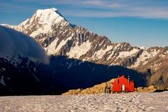La capanna rossa della montagna ed il Mt cucinano nei precedenti, Nuova Zelanda Fotografia Stock