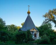 La cappella di legno ortodossa hiiden in alberi verdi fotografie stock