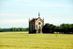 La cappella in un campo di grano accanto agli alberi si avvicina al comacchio in Italia fotografie stock libere da diritti