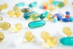 La capsula dell'olio di pesce e le pillole verdi, fuoco selettivo Fotografie Stock Libere da Diritti