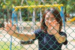 La captura adolescente asiática de la mano de la sonrisa soldó con autógena la cerca de alambre Fotos de archivo