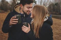 La captura de la forma de vida de los pares felices que beben el té caliente al aire libre en acogedor calienta el paseo imágenes de archivo libres de regalías