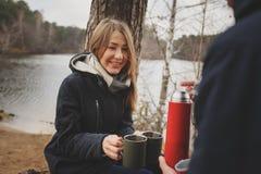 La capture de mode de vie des couples heureux buvant du thé chaud extérieur sur confortable chauffent la promenade Image libre de droits