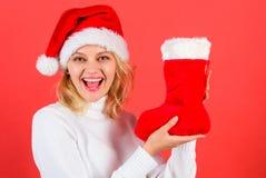 La cara alegre de la muchacha consiguió el regalo en calcetín de la Navidad Compruebe el contenido de la media de la Navidad Vaca imagen de archivo libre de regalías