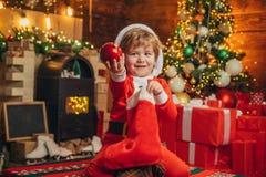 La cara alegre del ni?o consigui? el regalo en calcet?n de la Navidad Compruebe el contenido de la media de la Navidad Alegr?a y  imagenes de archivo