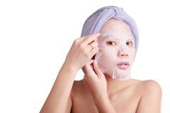 La cara asiática de la mujer joven, aplicación de la muchacha facial pela apagado la máscara foto de archivo
