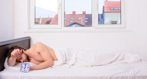 La cara barbuda sin afeitar soñolienta del hombre cubierta con combinado teniendo horario del sueño del palillo del resto la mism fotos de archivo