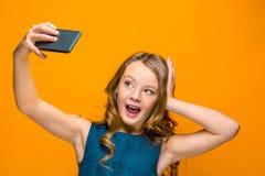 La cara de la muchacha adolescente feliz juguetona con el teléfono Foto de archivo libre de regalías