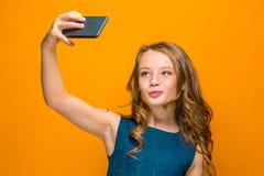 La cara de la muchacha adolescente feliz juguetona con el teléfono Fotos de archivo