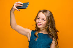 La cara de la muchacha adolescente feliz juguetona con el teléfono Fotografía de archivo