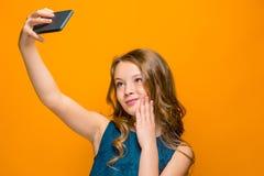 La cara de la muchacha adolescente feliz juguetona con el teléfono Imagen de archivo