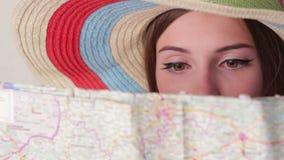 La cara de la muchacha detrás de un mapa almacen de metraje de vídeo